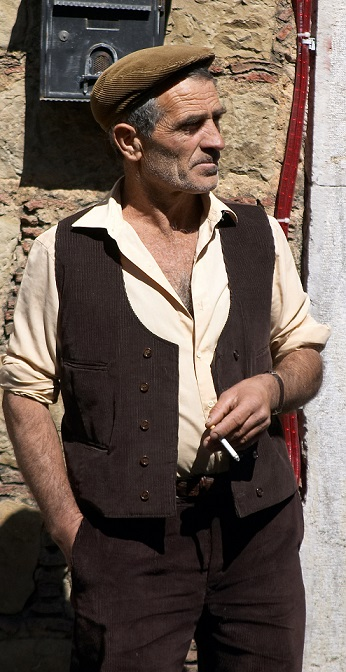 "A man wearing a ""coppola"", a traditional kind of flat cap worn in Sicily"